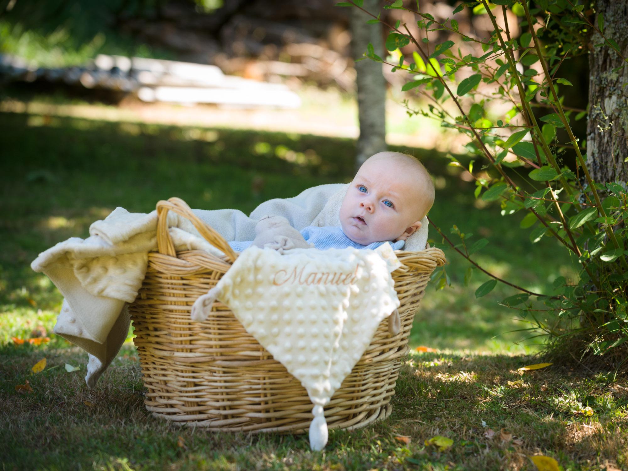 Fotografía de bebé dentro de cesto nun xardín. asestelo fotografía