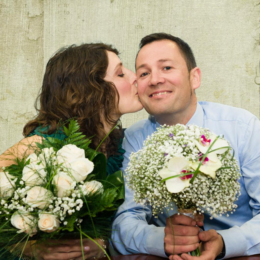 Retrato dos noivos de voda civil con ramo de flores.